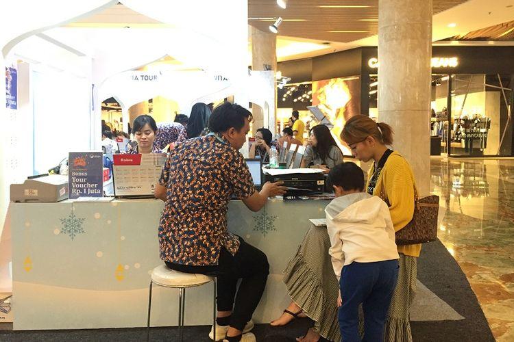 Seorang pengunjung Korea Travel Fair 2019  bersama anaknya sedang mencari paket wisata di salah satu stan agen perjalanan.