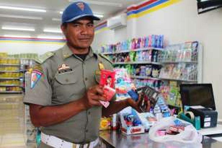 Seorang personel Satpol PP WH dan Linmas Aceh Tengah sedang memperlihatkan sejumlah temuan alat kontrasepsi dan alat yang berhubungan dengan hubungan seksual yang dijual bebas di minimarket Indomaret Takengon, Aceh Tengah, Aceh, Rabu (3/8/2016).