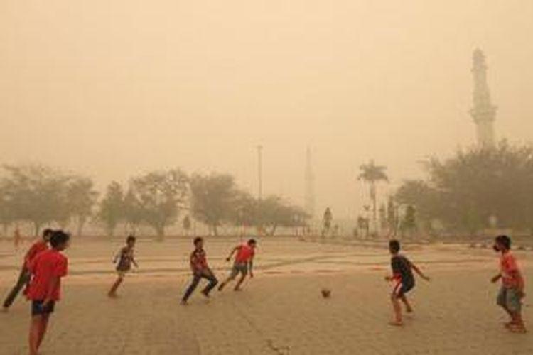 Sejumlah anak bermain bola di area Masjid Agung An Nur, Pekanbaru, yang diselimuti kabut asap, Kamis (13/3/2014).