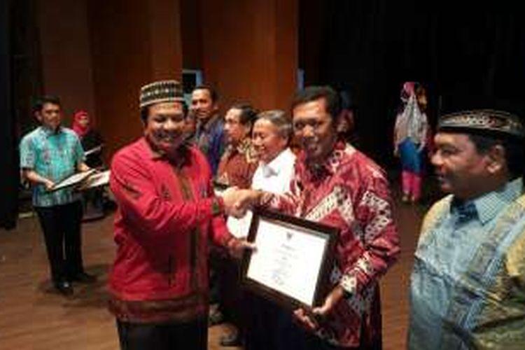 Sekretaris Daerah Aceh, Dermawan menyerahkan sertifikat Warisan Budaya Tak Benda Indonesia untuk Pacu Kude dan Tari Guel kepada Plt Bupati Aceh Tengah, Alhudri, Jumat (16/12/2016) malam, di Stage Indoors Taman Seni dan Budaya, Banda Aceh.