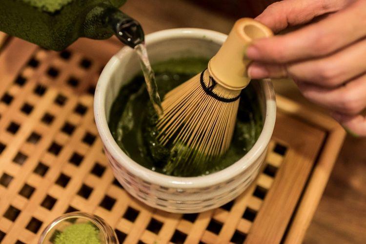 Matcha diseduh sambil diaduk-aduk dengan pengaduk terbuat dari bambu.