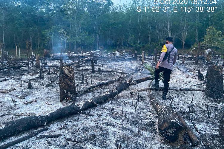 Salah seorang anggota polisi memeriksa lahan yang terbakar di Kabupaten Tabalong, Kalsel yang telah berhasil dipadamkan.