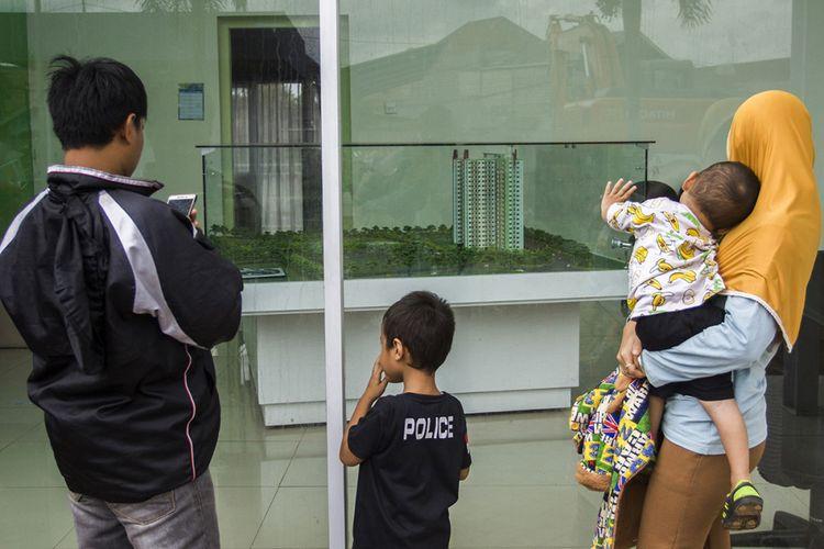 Warga melihat maket saat mencari informasi unit rumah susun dengan DP 0 Rupiah, di Kantor Informasi Klapa Village, Jakarta, Minggu (21/1/2018).
