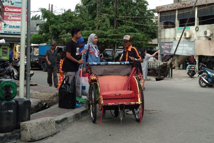 Warga menawar harga sebelum menggunakan becak di kampung Bahari, Tanjung Priok Selasa (12/1/2018). Becak masih menjadi pilihan warga untuk moda transportasi alternatif.