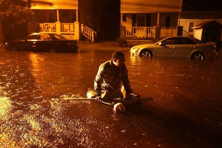 Seorang warga kota New Bern, Carolina Utara menaiki perahu darurat setelah air di Sungai Neuse yang meluap akibat badai Florence, Kamus (13/9/2018) malam.
