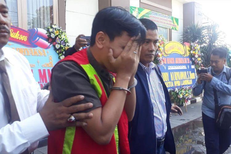 Tersangka AT (menutup wajah) usai diperiksa di kantor Kejari Lamongan dan hendak dibawa menuju mobil tahanan.