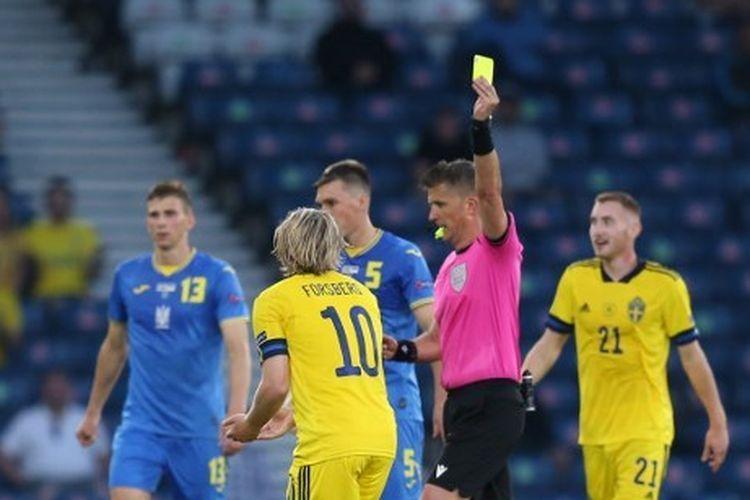 Pemain timnas Swedia, Emil Forsberg (tengah), diganjar kartu kuning karena melanggar gelandang Ukraina, Taras Stepanenko, dalam pertandingan Swedia vs Ukraina pada babak 16 besar Euro 2020 di Hampden Park, Glasgow, Skotlandia, Rabu (30/6/2021) dini hari WIB.
