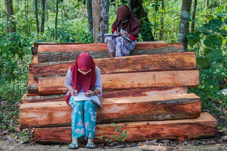 Sejumlah siswa SDN 1 Inten Jaya mengerjakan tugas melalui gawainya di Kampung Lebak Limus, Lebak, Banten, Senin (20/7/2020). Sejumlah siswa yang tinggal di daerah pelosok tersebut kesulitan dalam mengikuti kegiatan belajar mengajar (KBM) secara daring dan tepaksa menempuh perjalanan hingga satu kilometer dari kediamannya menuju ke dataran yang lebih tinggi agar mendapatkan jaringan internet guna mengerjakan tugas sekolah melalui gawai yang nantinya dikirim melalui aplikasi percakapan WhatssApp.