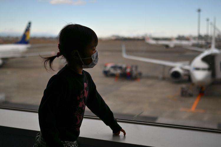 Seorang anak mengenakan masker saat berada di terminal keberangkatan Bandara Internasional Haneda, Tokyo, 31 Januari 2020. WHO menyatakan darurat global terkait penyebaran virus Corona, Covid-19.
