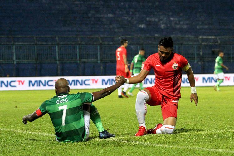 Pemain Persija Jakarta Maman Abdurahman membantu berdiri Pemain Madura United Greg Nwokolo saat semifinal Piala Gubernur Jatim yang berakhir dengan skor 2-1 di Stadion Kanjuruhan Malang, Jawa Timur, Senin (17/02/2020) malam.