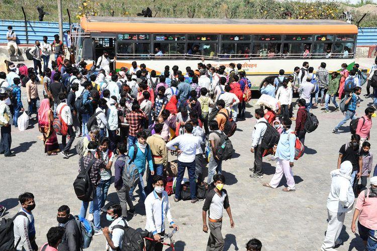 Pekerja migran memadati terminal bus di perbatasan Uttar Pradesh dekat New Delhi, India, pada 28 Maret 2020. Pemerintah Uttar Pradesh telah menyediakan 1.000 bus untuk pekerja migran yang hendak pulang ke desanya, tapi jumlahnya tidak mencukupi. Ratusan di antara pekerja itu lalu memutuskan pulang jalan kaki karena tidak ada transportasi yang tersedia. Situasi ini terjadi di hari keempat India menerapkan lockdown, yang berlangsung selama 21 hari sesuai instruksi Perdana Menteri Narendra Modi.