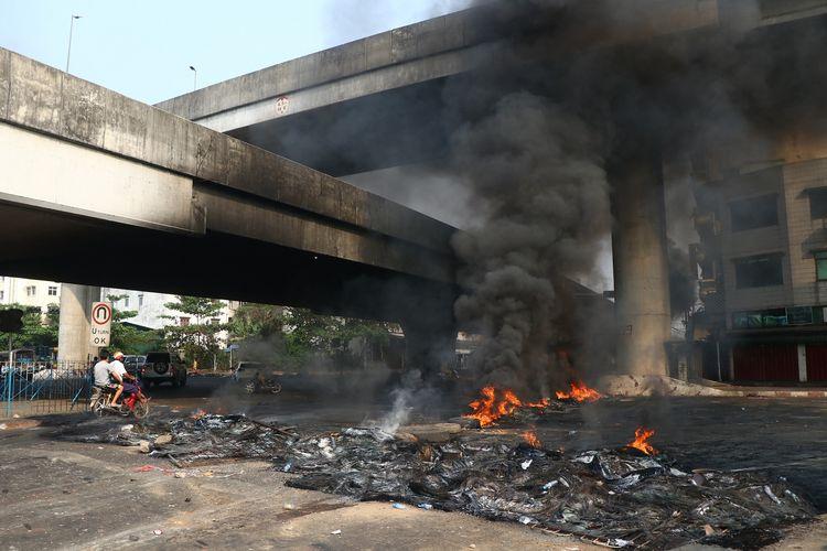 Pengendara sepeda motor melintas menembus kepulan asap sisa barikade yang terbakar di Yangon, pada Senin (15/3/2021).