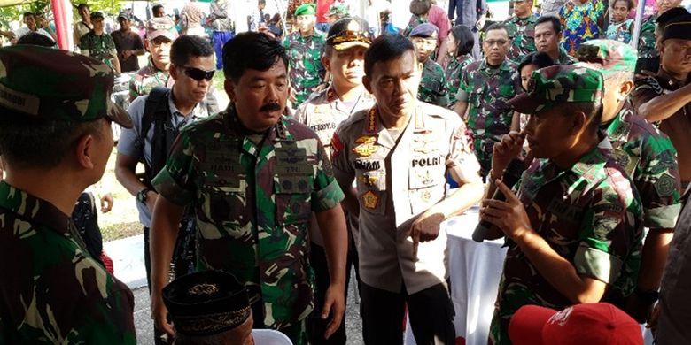 Panglima TNI dan Kapolri tengah melihat seorang warga yang sedang memeriksakan kesehatannya di acara Bakti Sosial TNI-Polri di PLBN Skouw, Kota Jayapura, Papua, Rabu (27/11/2019)
