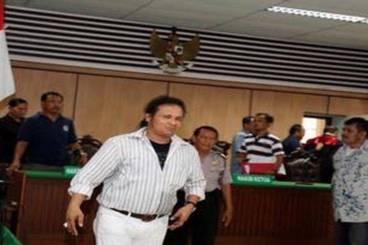 John Kei (bertopi) melenggang dan tak tampak cemas usai  dijatuhi vonis 12 tahun penjara oleh Majelis Hakim Pengadilan Negeri Jakarta Pusat, Jakarta, Kamis (27/12/2012). John Kei dinyatakan bersalah secara sah dan meyakinkan melakukan pembunuhan berencana terhadap Tan Harry Tantono alias Ayung. John Kei menyatakan akan banding.