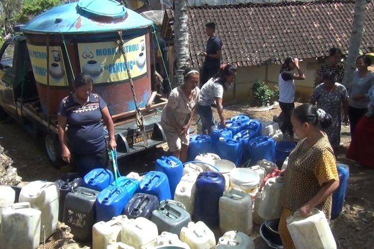 Warga desa Pandean tengah antri mengisi air dari tandon air mobil patroli Polisi sektor Dongko Trenggalek,Jawa Timur (06/09/2019)
