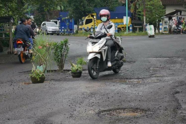 Seorang pengendara motor sedang melintas di antara pot tanaman milik warga yang diletakkan dijalan yang rusak Jumat (19/1/2017)