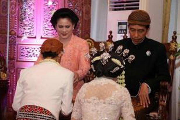 Presiden Joko Widodo dan Ibu Negara Iriana Widodo menerima sungkeman putranya Gibran Rakabuming Raka dan istrinya Selvi Ananda saat acara pernikahan di Solo, Jawa Tengah, 11 Juni 2015.
