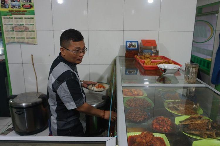 Sayudi sedang menyajikan makanan untuk pembeli di Warteg Kharisma Bahari di jalan Haji Batong Raya, kelurahan Cilandak Barat, Jakarta Selatan, Selasa (23/10/2018).