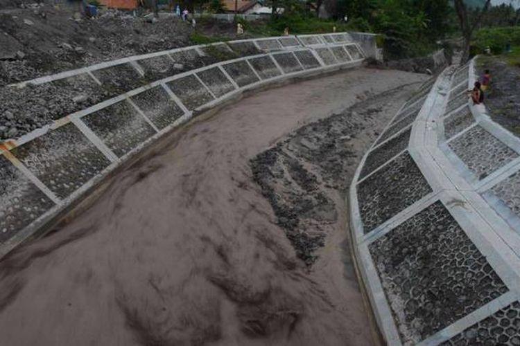 Warga menonton aliran banjir lahar hujan yang melewati Kali Putih di Desa Jumoyo, Salam, Magelang, Jawa Tengah, Selasa (25/12/2012). Hujan deras di kawasan lereng Gunung Merapi memicu terjadinya banjir lahar hujan yang membawa material sisa erupsi Merapi di sejumlah sungai di sisi barat Gunung Merapi. Banjir tersebut mengakibatkan satu buah mesin back hoe dan sedikitnya dua truk penambang pasir terjebak aliran banjir lahar hujan di Kali Senowo, Desa Mangunsoka, Kecamatan Dukun, Kabupaten Magelang.