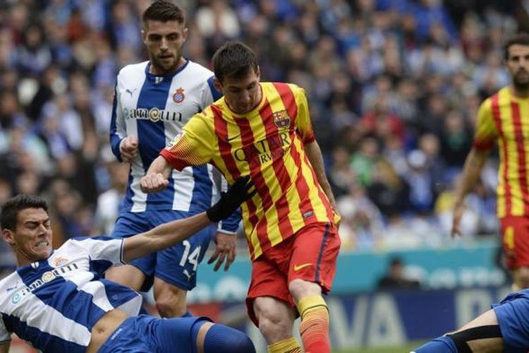 Striker Barcelona, Lionel Messi, saat berusaha melewati hadangan para pemain Espanyol pada lanjutan Liga BBVA di Stadion Cornella-El Prat, Sabtu (29/3/2014).