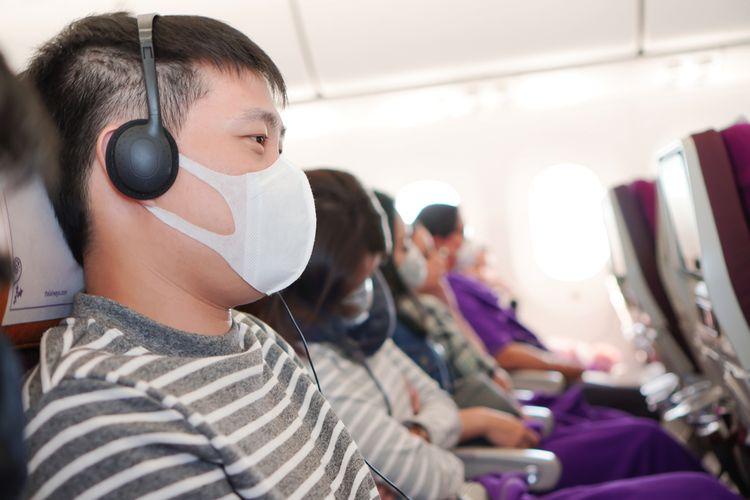 Ilustrasi penumpang menggunakan masker untuk cegah penyebaran virus corona di pesawat