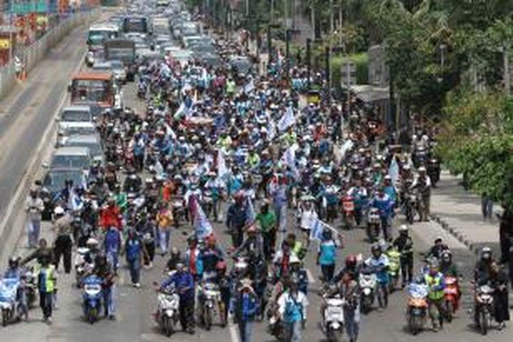 Massa buruh mendorong sepeda motor dalam unjuk rasa di Bundaran Hotel Indonesia, Jakarta Pusat, Rabu (10/12/2014), sebagai bentuk protes terhadap kenaikan harga BBM.
