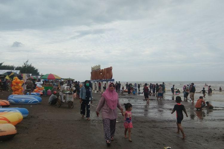 Pengunjung di Pantai Tanjungpakis, Desa Tanjungpakis, Kecamatan Pakisjaya, Jumat (1/1/2021).