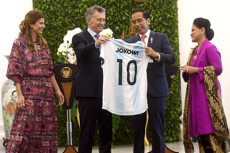 Presiden Joko Widodo (kedua kanan) didampingi Ibu Negara Iriana Joko Widodo (kanan) menerima seragam timnas Argentina dari Presiden Argentina Mauricio Macri (kedua kiri) dan istri Juliana Awada (kiri) usai pernyataan pers bersama di Istana Bogor, Jawa Barat, Rabu (26/6/2019).