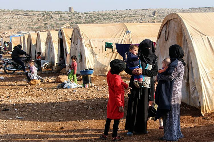Perempuan dan anak-anak terlihat di luar tenda di kamp Furat (Efrat) untuk orang-orang yang kehilangan tempat tinggal dari Deir Ezzor, sebelah utara kota Kafr Dariyan di provinsi utara Idlib, Suriah. Foto diambil pada 27 November 2017.