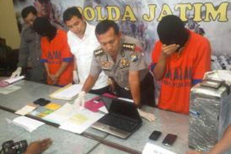 AR (kanan) pelajar yang mencuri pulsa dan voucher melalui sistem komputer.
