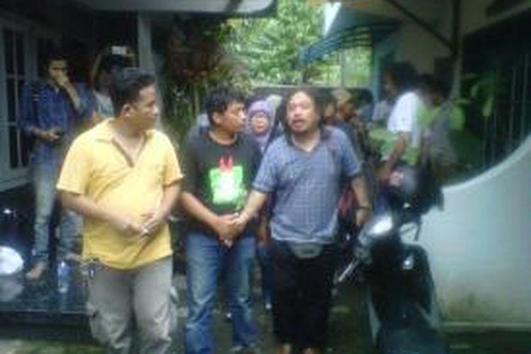 Saut Situmorang saat berjalan mengikuti tiga petugas kepolisan untuk dibawa kejakarta sebagai saksi