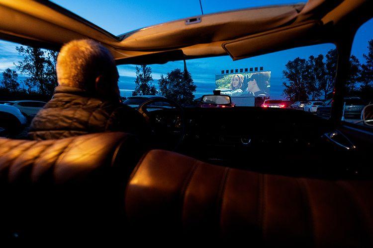 Seorang pria dari dalam mobil menonton film di Drive-in Cinema di Denia, Spanyol,  Kamis (14/5/2020). Bioskop drive-in dengan konsep menonton film dari dalam mobil yang sempat jaya dahulu kala, kini kembali menjadi tren di berbagai negara karena pandemi virus corona.