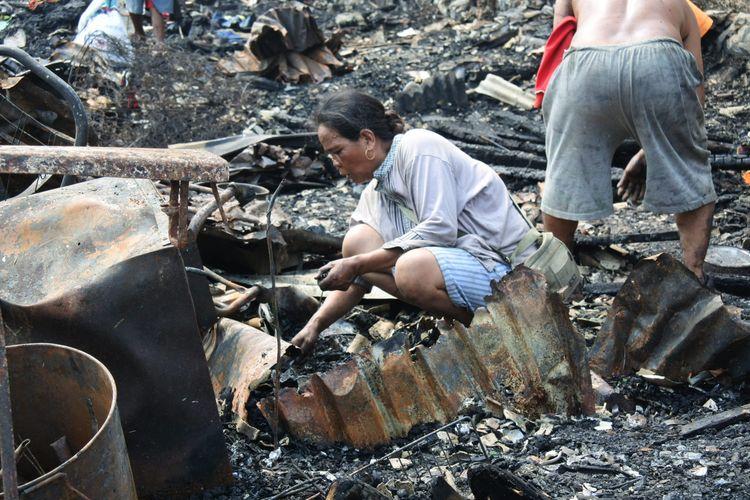 Seorang wanita mencari puing di tengah sisa kebakaran