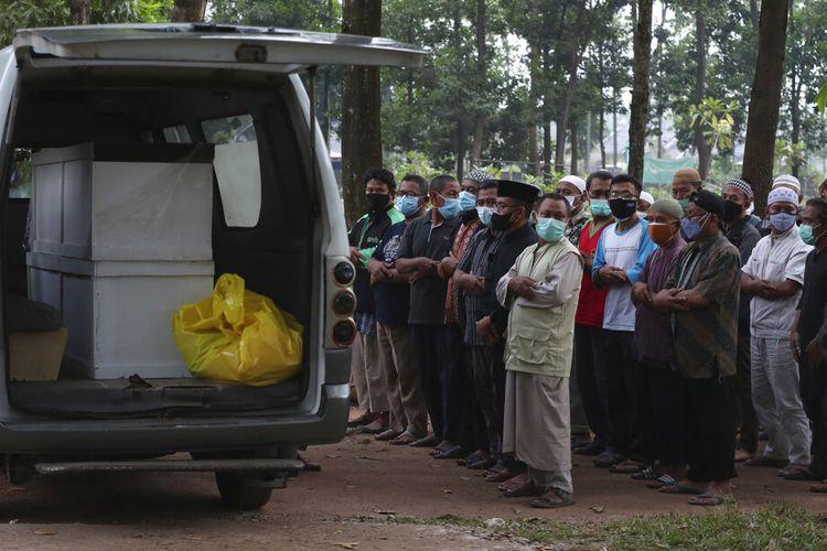 Warga berdoa di luar ambulans yang membawa peti mati dua korban COVID-19 sebelum dimakamkan di Pemakaman Cipenjo di Bogor, Jawa Barat, Indonesia, Rabu, 14 Juli 2021.