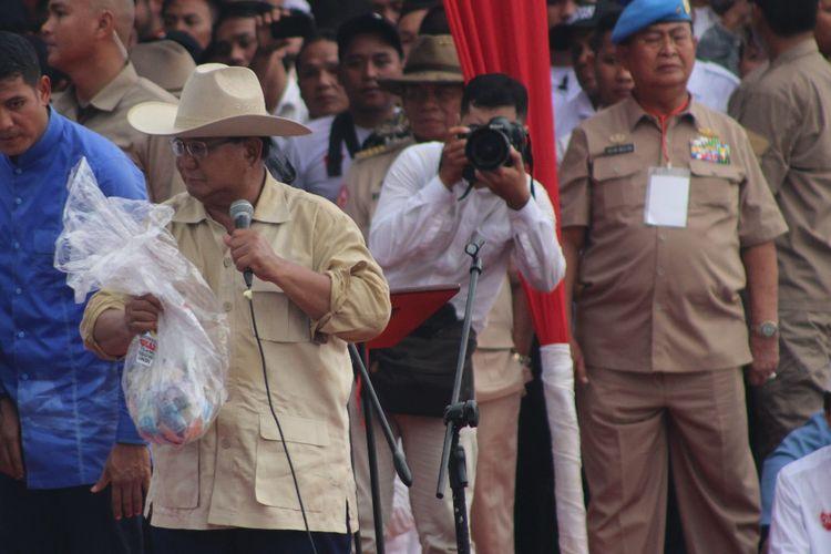 Calon Presiden nomor urut 02 Prabowo Subianto menunjukkan kantong plastik berisi uang saat menghadiri kampanye di pelataran Benteng Kuto Besak (BKB) Palembang, Sumatera Selatan, Selasa (9/4/2019).