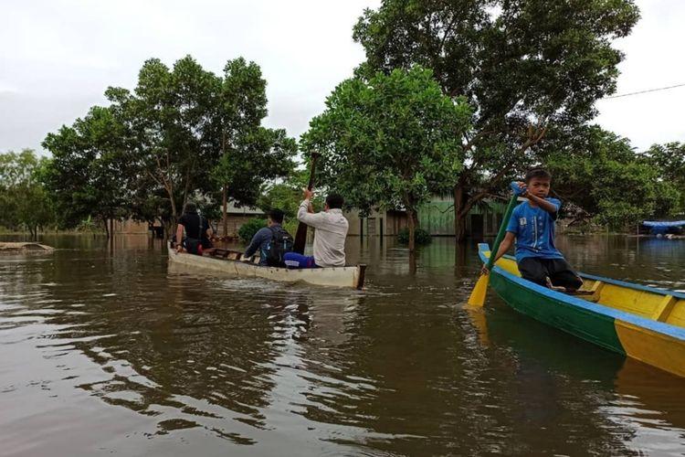 Warga Desa Laloika, Kecamatan Pondidaha, Kabupaten Konawe, Sultra terpaksa menggunakan perahu sebagai alat transportasi setelah banjir menerjang wilayah mereka. (Foto Istimewa)