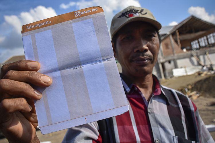 Turmuzi (35) asal Desa Obel-Obel menunjukkan saldo buku tabungan yang diperolehnya sebagai bantuan untuk korban gempa Lombok di Desa Pemenang Barat, Kecamatan Pemenang, Tanjung, Lombok Utara, NTB, Minggu (2/9/2018). Sebanyak 5.293 korban gempa dari Lombok Utara, Lombok Timur, Lombok Tengah dan Mataram menerima bantuan berupa tabungan sebesar Rp 50 juta untuk perbaikan rumah yang rusak berat dan Rp 25 juta untuk rumah yang rusak ringan.