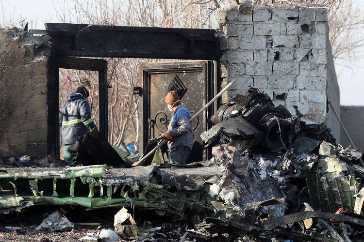 Petugas berkumpul di lokasi jatuhnya pesawat Ukraina di Parand, wilayah barat daya Teheran, Rabu (8/1/2020) pagi waktu setempat. Pesawat berjenis Boeing 737-800 itu jatuh tak lama setelah lepas landas dari Bandara Internasional Imam Khomeini, Teheran, Iran.