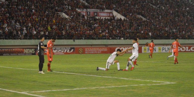Feby Eka Putra saat menarik tangan Aji Kusuma, usai pemain bernomor punggung 25 gagal membobol pertahanan Ade Chandra dalam laga antara Persis Solo Vs Timnas U-19 Indonesia, di Stadion Manahan, Solo, pada Senin (28/5/2018).