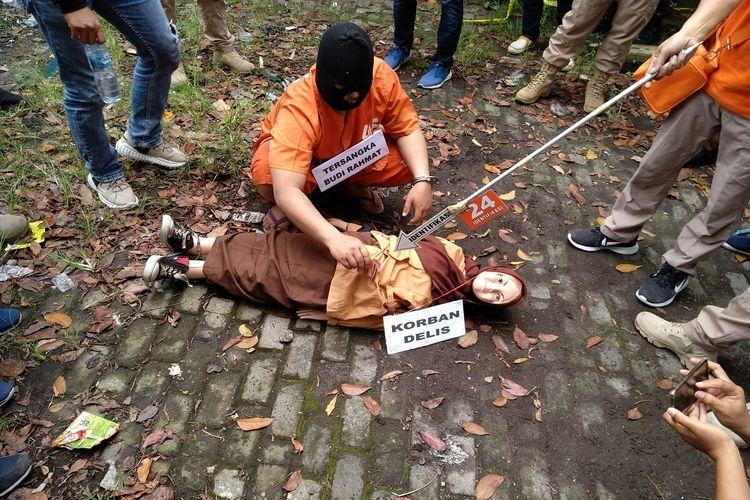 Budi Rahmat (45), pelaku pembunuhan anaknya sendiri saat melakukan reka adegan rekonstruksi di lokasi kejadian pembunuhan dan pembuangan mayat korban di gorong-gorong SMPN 6 Tasikmalaya, Kamis (12/3/2020).