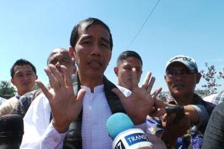 Gubernur DKI Jakarta Joko Widodo menunjukkan garia tangannya kepada wartawan untuk membuktikan pernyataan Wakil Gubernur DKI Jakarta Basuki Tjahaja Purnama yang menyatakan kalau garis tangan Jokowi adalah menjadi presiden.