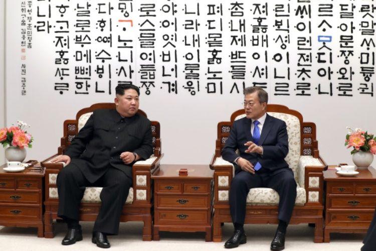 Pemimpin Korea Utara Kim Jong Un (kiri) ketika berbicara dengan Presiden Korea Selatan Moon Jae In saat Konferensi Tingkat Tinggi di Panmunjom Jumat (27/4/2018).