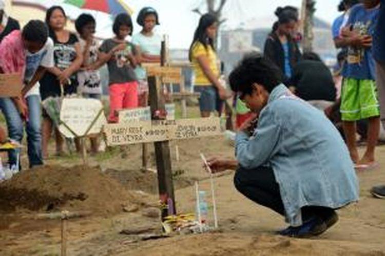 Seorang pria duduk berdoa di pusara keluarganya yang tewas akibat bencana Topan Haiyan yang menhantam wilayah tengah Filipina November lalu. Sejauh ini, pemerintah Filipina menyebutkan lebih dari 6.000 orang dinyatakan tewas akibat bencana tersebut.