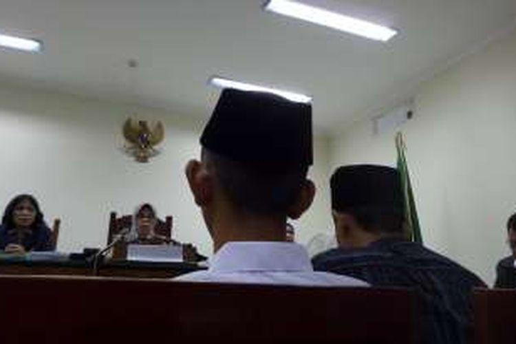 Remaja terdakwa kasus pembunuhan karyawati EF (19), RA (16), mendengarkan putusan di Pengadilan Negeri Tangerang, Kamis (16/6/2016). Pada sidang putusan ini, RA didampingi ayahnya, Nayudin, yang duduk di sampingnya.