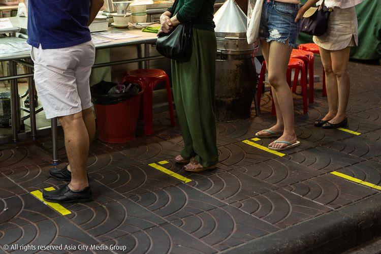 Terlihat garis-garis pembatas yang ditempel di perumukaan trotoar untuk membatasi jarak antar pembeli yang sedang mengantre membeli makanan di Yaowarat, Bangkok, Thailand