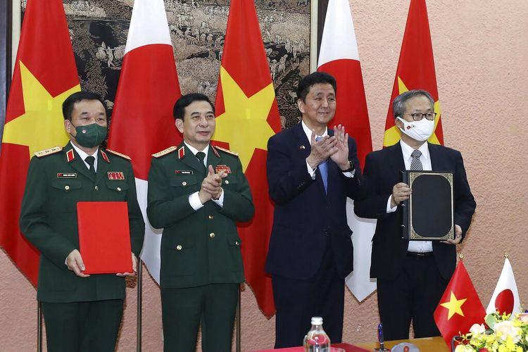 Menteri Pertahanan Vietnam Phan Van Giang, kiri tengah, dan Menteri Pertahanan Jepang Nobuo Kishi, kanan tengah, berfoto bersama pejabat mereka setelah menandatangani kesepakatan di Hanoi, Vietnam, Minggu, 12 September 2021.