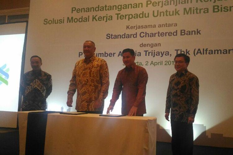 CEO Standard Chartered Indonesia Rino Donosepoetro dan CEO Alfamart Hans Prawira menandatangani kerja sama modal solusi kerja terpadu di Hotel Shangri-La Jakarta, Senin (2/4/2018).