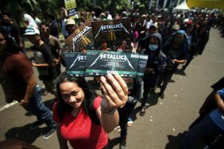 Calon penonton konser Metallica menunjukkan tiket yang telah dibelinya di Stadion Utama Gelora Bung Karno, Sabtu (24/8/2013). Band heavy metal asal Amerika Serikat tersebut akan menggelar konsernya besok Minggu, 25 Agustus.