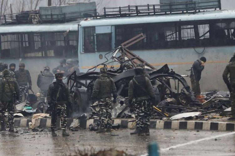 Pasukan keamanan India memeriksa sisa-sisa kendaraan yang hancur diserang bom bunuh diri oleh kelompok pemberontak Pakistan, Jaish-e-Mohammad, di dekat kota Awantipur, Lethpora di Kashmir, Kamis (14/2/2019). (AFP)