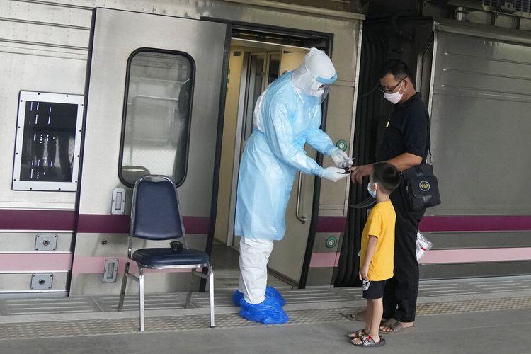Seorang petugas kesehatan memeriksa kadar oksigen untuk pasien Covid-19 setibanya di stasiun kereta Rangsit di provinsi Pathum Thani, Thailand, Selasa, 27 Juli 2021.